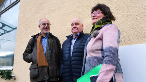 Två medelålders män och en medelålders kvinna i ytterkläder står framför en gulrappad vägg. Personerna ler men ingen av dem ser in i kameran.