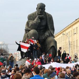 Ihmisjoukko patsaan edustalla ja ympärillä.