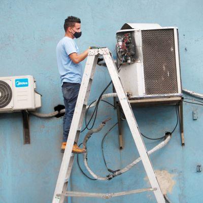 Mies korjaa ilmastointilaitetta Kuubassa.