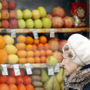 En kvinna går förbi en fruktbutik i Moskva.
