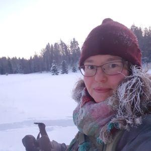 En kvinna ute i ett snötäckt landskap.