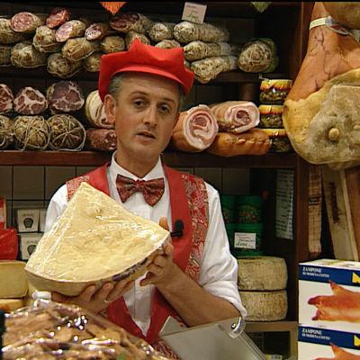 Bolognalainen kauppias kädessään iso parmesaanikimpale, takana hyllyillä erilaisia makkaroita, kinkkua, juustoja.