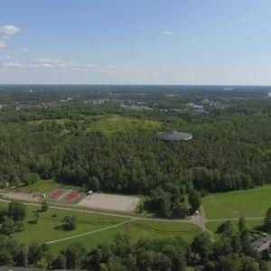 Luftvy över Luolavuori stadsdel, där man ser ett skogsparti med ett runt vattentorn sticka upp, samt tennisplaner och en bilväg.