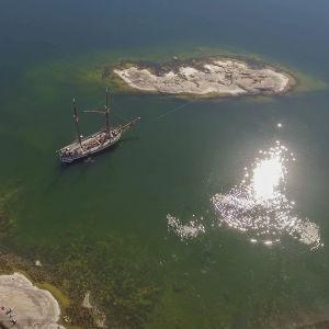 Ilmakuva Dalskär-saaresta ja purjealus kaljaasi Olgasta.