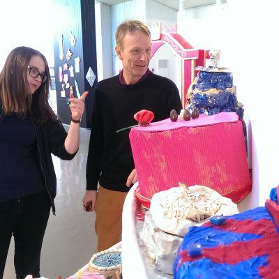 Kuvataidekoulun oppilas Johanna Hiekkala ja koulun rehtori Klaus Savolainen tutkivat tarkemmin juhlanäyttelyn kakkutarjontaa.