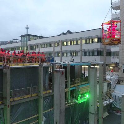 Kuopion yliopistollisen sairaalan rakennustyömaa, jossa työmiehet ja joulupukki vilkuttavat lapsille, jotka katsovat sairaalan ikkunoista.