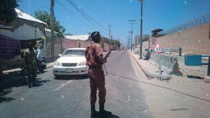 Säkerhetsvakt hoppar ut ur bilen mitt under bilfärden i Mogadishu.