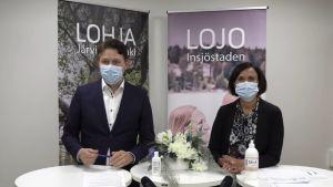 En man i kostym och en kvinna i mörka kläder ser in i kameran. Båda har munskydd och i bakgrunden finns affischer med texterna Lojo-Lohja.