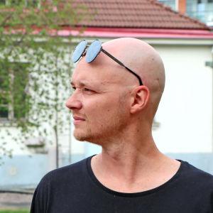 Fredi Lundén tittar åt vänster, poserar med solglasögon på pannan.