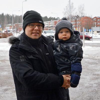 En man står på en parkeringsplats med ett barn i famnen.
