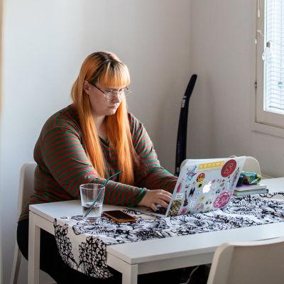 En kvinna med orange hår sitter och jobbar på en dator vid ett vitt köksbord.