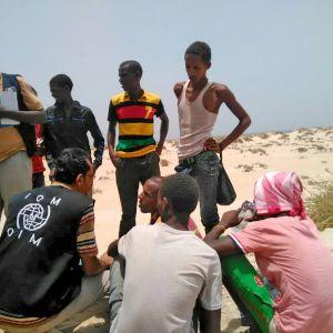 Överlevande migranter på en strand i södra Jemen. Runt 100 flyktingar befaras ha drunknat utanför Jemens kust efter att ha tvingats i havet av människosmugglare.