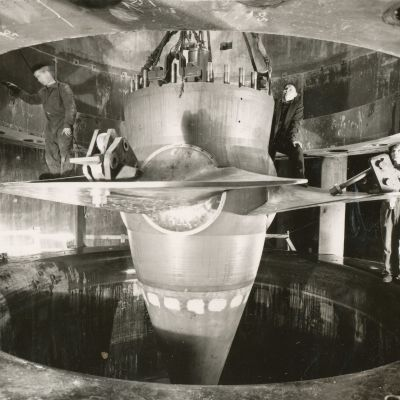 Työmiehiä turbiinin juoksupyörän siivillä, kun sitä lasketaan turbiinin kammioon. Kuvattu 12.5.1959.