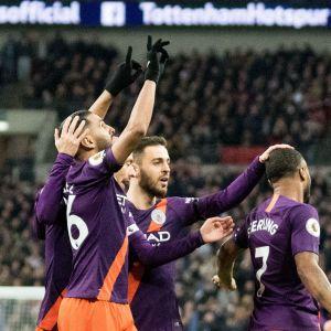 Riyad Mahrez sträcker händerna i luften samtidigt som han gratuleras av sina lagkamrater.