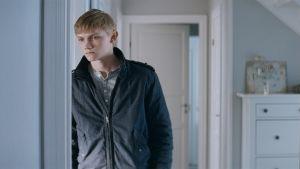 Huvudpersonen John lutar mot en dörrpost.