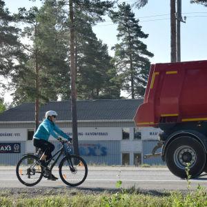 En cyklist cyklar på en riksväg. Framför cyklisten kör en lastbil.