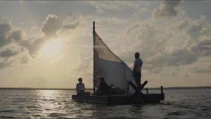 Huvudpersonerna i filmen sitter på en liten flotte och seglar mot horisonten.