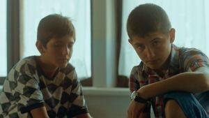 Två av pojkarna i den stökiga klassen sittande på pulpeten.