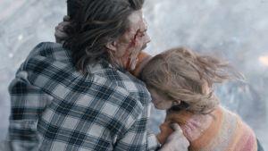 Far och dotter klmarar sig fast vid varandra medan världen rasar sönder omkring dem.