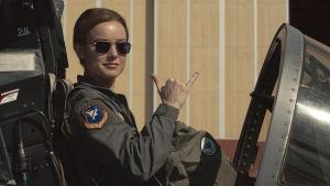 Brie Larsons Captain Marvel sitter i cockpiten på ett stridsflyg.