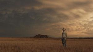 en ensam cowboy står och tittar ut över ett öppet landskap.