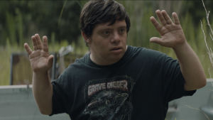 Zak (Zack Gottsagen) står med händerna uppe och ser rädd ut.