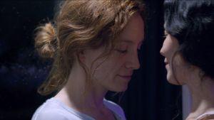 Närbild på Mimaroben (Emelie Jonsson) och Isagel (Bianca Cruzeiro) som står mittemot varandra.