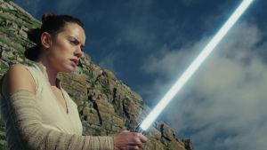 Rey (Daisy Ridley) tittar förundrat på sitt lasersvärd.