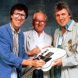 Hank Marvin, Brian Bennett och Bruce Welch i The Shadows håller i en elgitarr som de signerar.