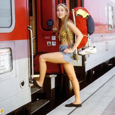 Nainen nousee rinkka selässään junaan Saksassa.