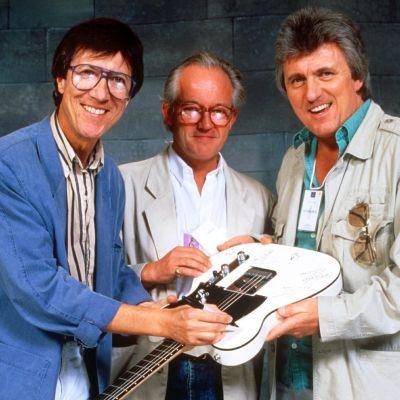 Hank Marvin, Brian Bennett och Bruce Welch i The Shadows håller i en elgitarr som de signerar.