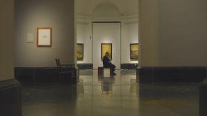 Roy Andersson fotograferad på lång håll på ett museum bland tavlor av Goya.