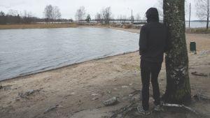 En ung man bakifrån vid en sjö