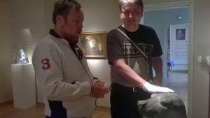 Patrik Paulin och Andreas Kanto känner på en skulptur föreställande ett sälhuvud.