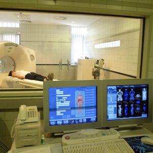 Kvinna ligger i skiktröntgen-apparat, datortomografi