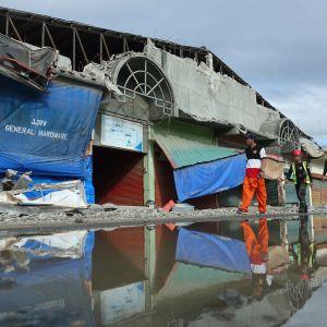 Huomioliiveihin pukeutuneet pelastajat kävelevät maanjärjistyksen runteleman kauppahallin ohi Padadan kaupungissa Filippiineillä. Osa rakennuksen julkisivusta on sortunut järistyksen takia.