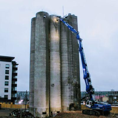 Purkukone työn touhussa. Purkukone yltää 43 metrisen siilojen huipulle, jossa se pikku hiljaa nakertaa betonia irti rakennuksesta.
