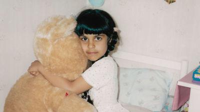 Ett barn med långt svart hår sitter på en säng och kramar en stor ljusbrun nalle.