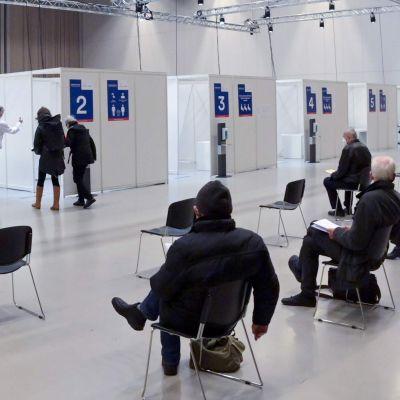 Människor väntar på att få en covid-19-vaccinering på ett vaccineringscentrum i Berlin