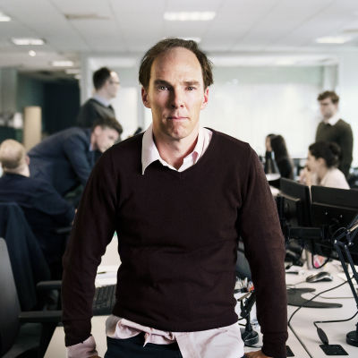 Benedict Cummings i rollen som den brittiska politiska strategen Dominic Cummings sitter på ett kontorsbord och ser rakt in i kameran.