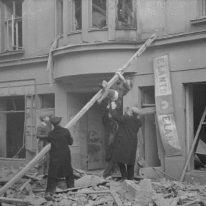 Ensimmäisen ilmapommituksen jälkeen tyttöä pelastetaan Lönnrotinkadulla kerrostalosta 30. marraskuuta 1939. Koira katsoo ikkunasta.