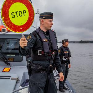 En sjöbevakare står med ett stop-märke i handen på en båt. I bakgrunden syns vatten.