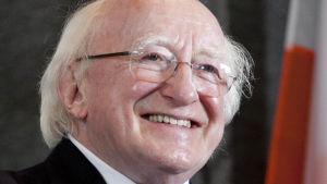 Irlands president, en äldre herre med vitt hår i kostym och slips, ler mot kameran.