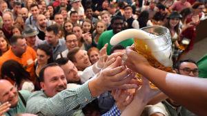 Folk sträcker sig efter ett ölstop på Oktoberfest.