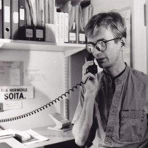 Nuori Jussi Nissinen 1986 puhuu lankapuhelimeen Seta ry:n toimistolla.
