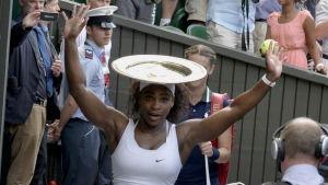 Serena Williams med segerpokalen på huvudet.