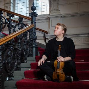 viulisti Pekka Kuusisto istuu viulu kädessä portaikossa