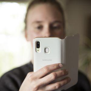 Henkilö pitelee puhelinta kasvojen edessä.