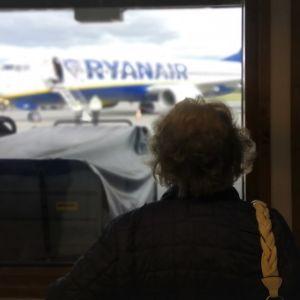 Iäkäs nainen seuraa ikkunasta Ryanairin koneen laskeutumista