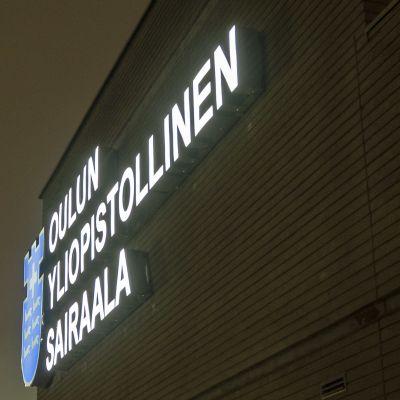 Oulun yliopistollisen sairaalan valologo seinässä.